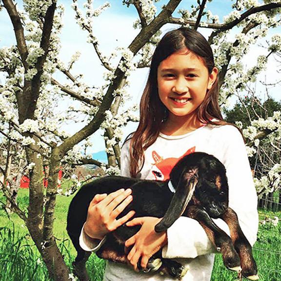 Nicole holding a newborn baby goat kid